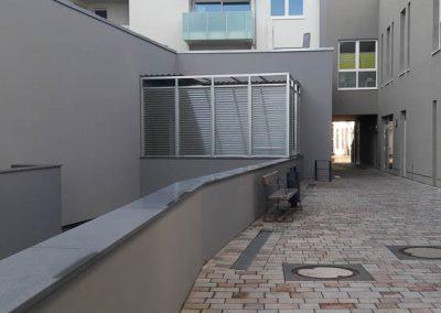 Innenhof von Wohnhäusern mit Sicht auf Balkone mi Milchglasscheiben