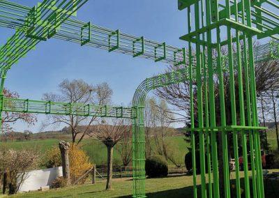 Grünes Metallgestell im Garten für Pflanzenranken