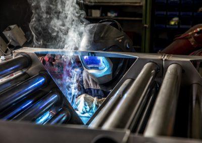 Schweißer schweißt mehrere Metallrohre zusammen