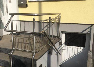 Treppengeländer aus Metall vom EIngang runter zum Keller an einem gelben Haus befestigt