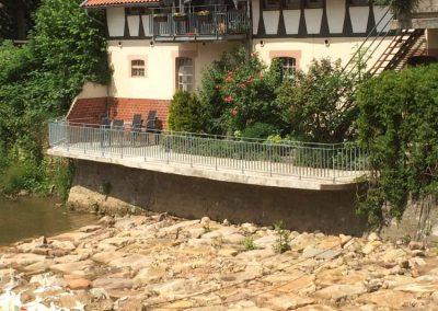 Metallgeländer an einem Balkon, darunter ist ein großes ausgetrocknetes Flussbett