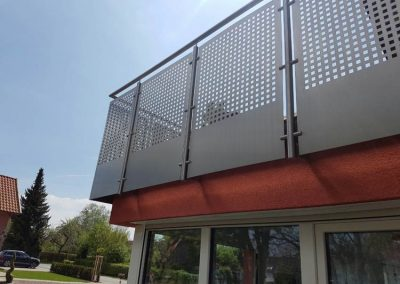 Balkongeländer an einem roten Haus mit quadratischen Metallplatten