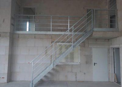 Metallgittertreppe mit Balkongeländer in einer Industriehalle