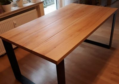 hellbrauner Holztisch mit schwarzen Metallbeinen