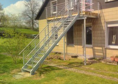 Metalltreppe, die vom Balkon herunter in den Garten führt