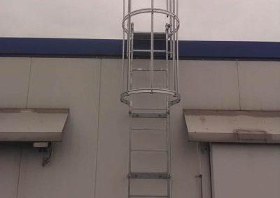 Metallleiter mit runden Absturzschutz an einer Hauswand